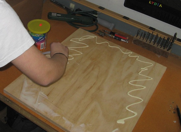 Gluing together the layers of the guitar frame.