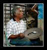 Great Master, Salvador Vasquez, at his home workshop in Tonola demonstrating his skill with clay to LADAP in 2002.  He is well known for his use of naguals on pottery & is painting one in the center of this plate.