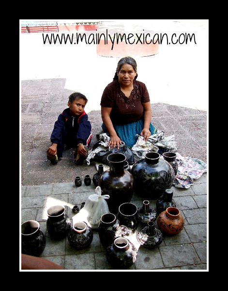 Grand Master potter, Elena Felipe of Zamora, Michoacan selling several of her pieces in Ajijic - she and two other artisans came by bus for the day to try to make some sales.  Michoacan state has no tourists or retail sales of artisania currently due to continual bad news related to drug cartels.  We purchased most of these pots and many others from her at an average of $10 USD each. September 2009
