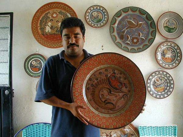 "The son of Salvador Vasquez made the 22"" charger he is holding which features a large nagual in the center.  Other plates on the wall made by Salvador.  LADAP visited in 2002"