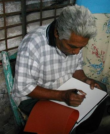 """Salvador Vasquez signing the book about him """"Nagual in the Garden:Fantastic Animals in Mexican Ceramics"""" by Lenore Hoag Mulryan during a visit by LADAP in 2002"""