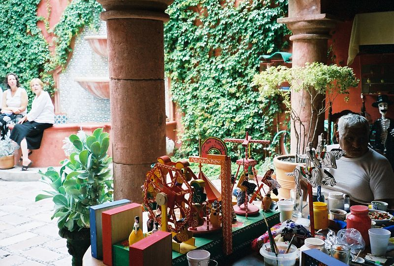 "This is ""Great Master,"" Gumercindo Espana Olivares demonstrating his work on toys on the patio of Casa de la Cuesta in San Miguel de Allende during the rendezvous of Los Amigos del Arte Popular in July 2004.  For more information, see ""Great Masters of Mexican Folk Art"" pages 218-221."