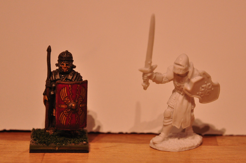 Left: Wargames Foundry metal Roman legionary, 30mm feet to helmet<br /> Right: Garrick The Bold, Reaper Bones miniature, 35mm feet to helmet<br /> <br /> Both are 28mm scale...