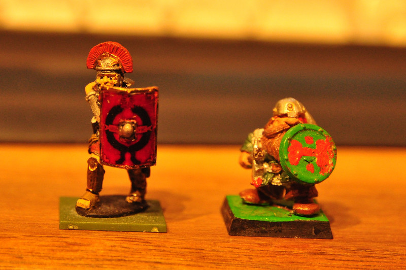 Scale comparison, both are 28mm scale.<br /> Left: Modern Warlord Games mini of a Roman centurion.<br /> Right: Games Workshop Dwarf 1986.<br /> <br /> Notice the head, hands and feet.