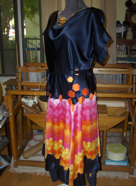 "The Resistance Dress.  As a fan of the band Muse I saw the pink and orange fabric and immediately thought of their Resistance album cover. In searching for inspiration to transform the image into a garment I looked through designs by Madeline Vionnet  and found my muse in bias draped silk. I cut along the hexagon  design and then appliqued it at hip level to the bias draped bodice.  I debated about putting a ""starfeild"" of rhinestones on the blue silk, but decided against it."
