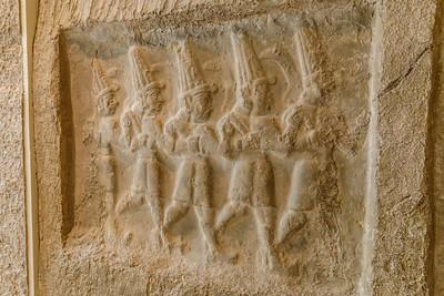 """Ischtar Schcıwuschka und andere Göttinnen lm Gefolge des mönnlichen Hauptgottes des Götterzuges der Großen Kammer befindet sich auch eine Göttin nebst zwei Dienerinnen. Die Göttin ist geflügelt und trägt eine hohe Spitzmütze sowie ein langes, schleppenartiges Gewand, das ein Bein freigibt. Zwei Dienerinnen folgen ihr, mit runden Kappen und gegürteten, in Falten bis über die Füße herabfallenden Röcken bekleidet. Sie tragen einen Striegel bzw. einen Spiegel in den Händen, also weibliche Attribute, wöhrend die Göttin selbstdurch eine Zuordnung zum Zug der männlichen Gottheiten einen männlichen Aspekt, wohl den der Kriegsgottheit, wiedergibt, also zweigeschlechtlich gedacht wurde. Die Namenshieroglyphe benennt sie als Scha(w)uschka, die hurritische Form der lschtar, während die beiden Dienerinnen dementsprechend als Ninatta und Kulitta bezeichnet werden können. Links neben den Göttinnen, im Original von diesen durch weitere Gottheiten getrennt, tragen zwei auf dem Symbol """"Erde"""" stehende Stiermenschen das Symbol """"Himmel"""" ; sie können als die göttlichen Stiere Scheri und Hurri verstanden werden."""