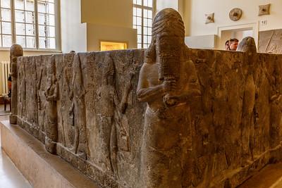 Wasserbecken, Waterbasin Assur, Basalt, 704-681 v.Chr. Ashur, 704-681 BC Das ursprünglich aus einem großen Basaltblock herausgehauene Becken wurde völlig zersplittert in einem der Höfe des Assur-Tempels gefunden. Es konnte unter Verwendung vieler Originalteile rekonstruiert werden. An den Ecken und in der Mitte jeder Seite sind Wassergötter mit überquellenden Gefäßen abgebildet. Die Wasserstrahlen kommen von oben - vom Himmel - und enden unten - in der Erde. ln den Zwischenräumen stehen mit Fischhäuten bekleidete Priester, die Eimer und kleine Kultgeräte in den Händen tragen. Eine mehrfach wiederholte Keilinschrift nennt den Namen des Königs Sanherib (704-681 v.Chr.). Die Innenflächen des Beckens sind undekoriert. Das Becken wurde vermutlich für kultische Reinigungen von Priestern und Gläubigen benutzt.
