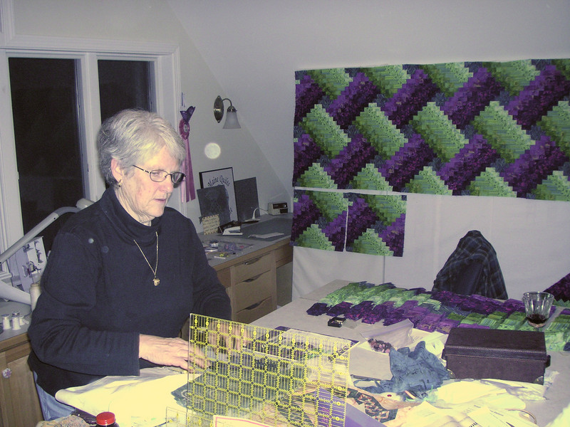 The artist at work in her loft.  Completed squares on the wall, partially completed squares stacked on the island.