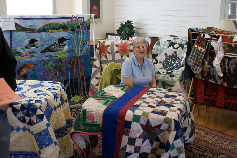 "Here she is as the ""Featured Quilter at a recent show - surrounded by some of her creations.  I like most of these, especially the ""Loon"" (back left), ""Iris"" (behind her, to the right).  The blue and white one (left, front) is _very_ complicated and interesting."
