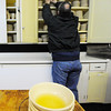 Rollstone Congregational Church Pastor Dave Hanks talks pulls out bowls in the church's kitchen on Thursday where standing water sits inside the dishes after water poured down to the lower floors after frozen pipes burst recently.<br /> SENTINEL & ENTERPRISE / BRETT CRAWFORD