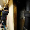 Cleghorn Plumbing employee Alex Medino of Fitchburg works on the broken water lines in Rollstone Congregational Church on Main St. in Fitchburg on Thursday after the pipes burst due the recent cold weather. <br /> SENTINEL & ENTERPRISE / BRETT CRAWFORD
