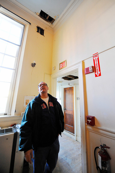 Rollstone Congregational Church Pastor Dave Hanks talks on Thursday in the fellowship hall about the water damage that occurred at the church after frozen pipes burst recently. Cut holes in the wall and ceiling can be seen where broken pipes were accessed to be worked on.<br /> SENTINEL & ENTERPRISE / BRETT CRAWFORD