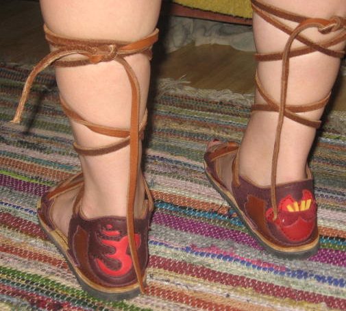 Here is the back view of Cypress' new birthday sandals - Om on the left shoe, in red deerskin set in redwood deerksin trim.  On the right shoe is a lotus flower done in two shades of red, with gold stamen, set in redwood deerskin.<br /> The 'long laces' haven't been trimmed yet.
