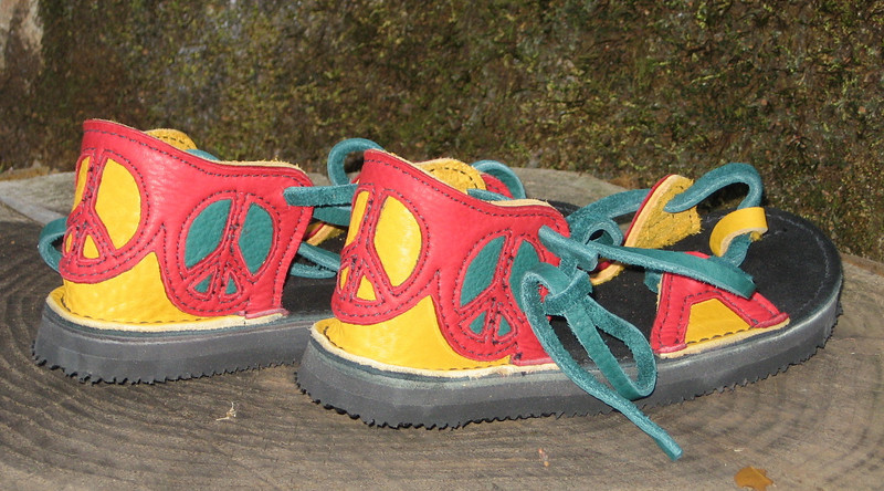 Rasta Peace Girl... Isn't her design beautiful!  <br /> Two Tab Sandals, Gold Bullhide, Red Deerskin Trim, Peace Sign Cutouts, Green Deerskin Underlay, Green Laces, Thin Cushi, Spikeless Golf Soling