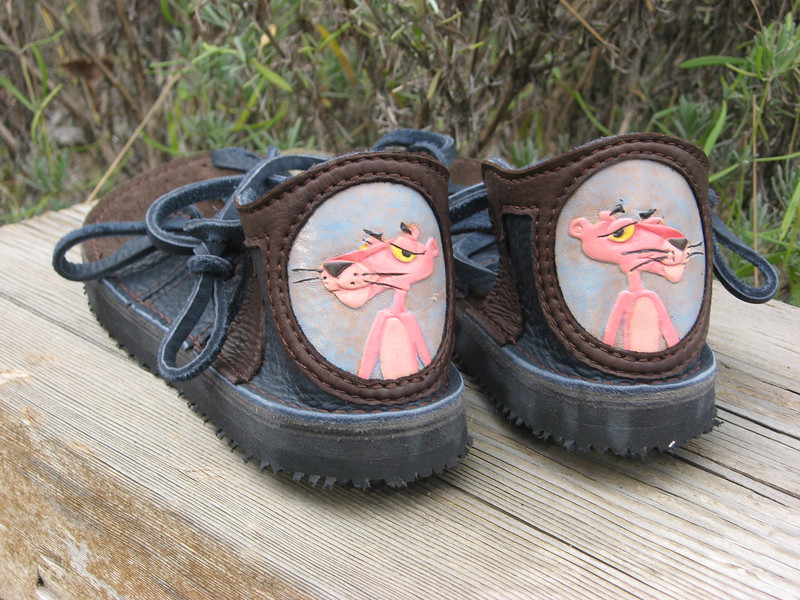 Sweet Susan loves the Pink Panther!  I was able to find some wonderful leather working folks who tooled and painted the design for her sandals.  Fun!<br /> Four Tab Sandals, Navy Bullhide, Chocolate Deerskin Heel Trim, Pink Panther Tooled Inset, Thin Cushi, Spikeless Golf Vibram Soling.