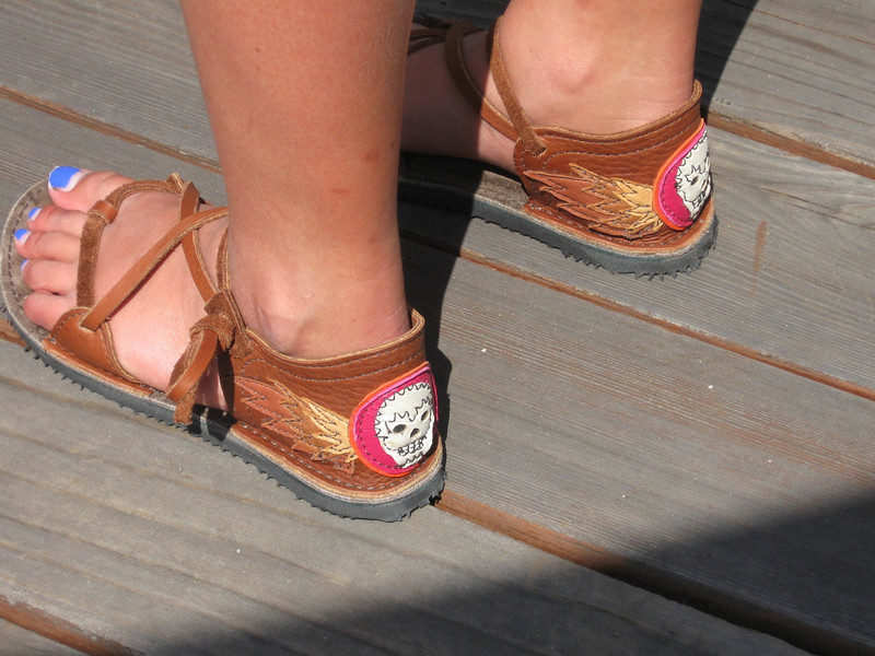 Hannah's 2-tab sandals have a sugar skull in white with black embroidery on the heels.  The skulls are set on fuschia and orange circles, with wings of various colors of deerskin layered behind.  The soling is newflex vibram.
