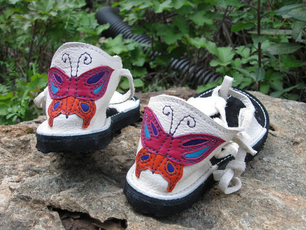 Butterflies... transformation...<br /> This pair of two tab sandals are made from white buffalo hide - which is about half as thick as the regular buffalo hide.  She chose a black footbed, white stitching, and a deerskin applique butterfly for the heels.  Newflex Vibram soling finishes them off.