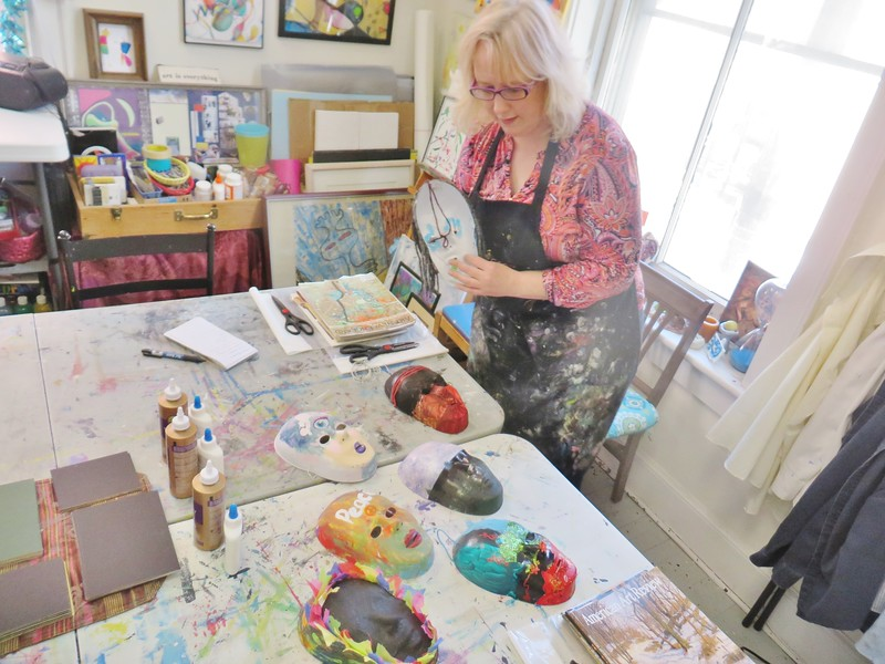 Pittsfield-based arts therapist Marney Schorr shows off a group of masks created by teens and young adults in her Arts in Recovery for Youth studio program.