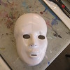 Each student receives a blank mask to sketch a design on.