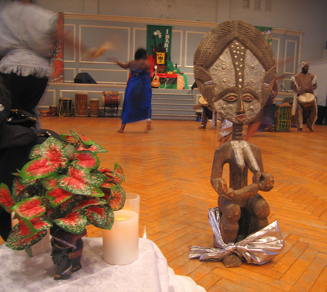 Plant and statue, dancers in bg