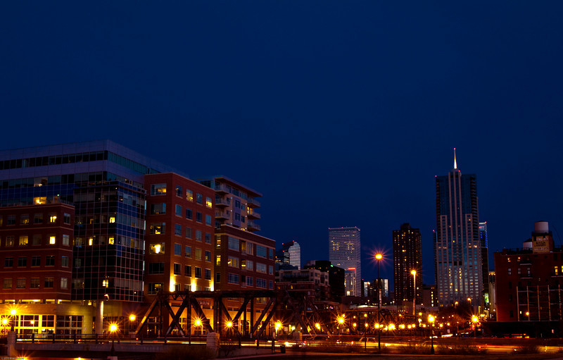 The Denver skyline seenfrom Speer Avenue. In the foreground is the Wynkoop Street bridge.