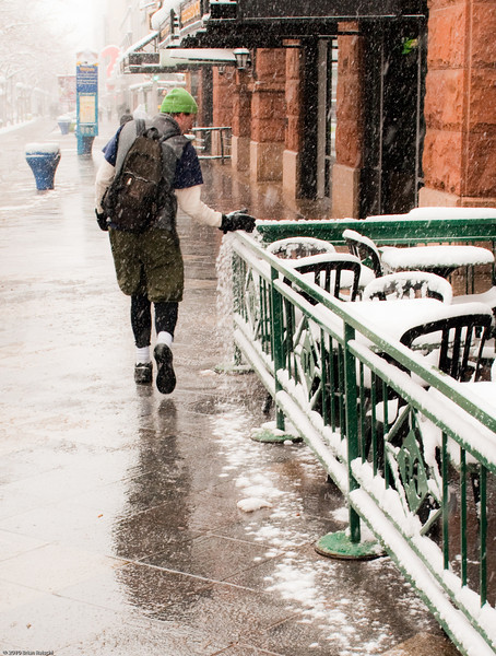 I aws out shooting during one of Denvers many spring snowstorms. Several inches of wet snow had stuck to every flat surface. Just after I finished shooting some photos of this cafe this guy walked by. He swept all the snow off of fifty feet worth of railing. I think it was just for the fun of it.<br /> <br /> I wish he'd left some of that snow for me!