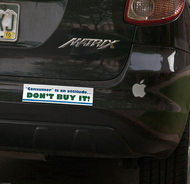 "This car frequently parks near my house. I wonder if the owner understands the irony of his bumper stickers. ""Consumerism is an attitude - DON'T BUY IT!"" right next to the logo of a consumer electronics company."