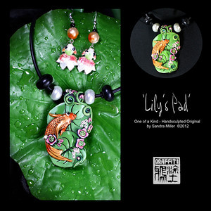"LILY'S PAD KOI NECKLACE AND EARRING SET  Mz Lily the Koi wants to invite you over to her 'pad' for some green tea and mooncakes!  Her little cloisonne earring friends ""Bud"" and ""Blossom"" said they will bring fortune cookies!  This elegant koi has an iridescent finish and is surrounded by hand applied floral elements all the way over the top of the bail as well.  2 large pearlized glass beads flank the pendant with genuine Swarovski crystals studding the lilypads.  The earrings feature vintage lucite swirl beads from an old estate sale bracelet I rescued!  PENDANT MEASURES   2 1/2  x 1 1/2""   Neoprene cord is finished at the back with chain and adjusts from 16-20"" long."