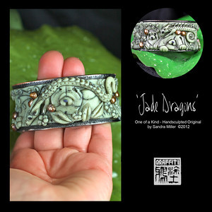 "JADE DRAGONS-CLICK HERE TO VIEW VIDEO DESCRIPTION IN A NEW WINDOW  Exquisite hinged cuff bracelet in Faux Jade  I created JADE DRAGONS to commemorate Chinese New Year 2012-Year of the Dragon!!!  Ever since my 2011 Trunk Show I have received dozens of requests to repeat the elaborate cuff bracelet I made.  I finally found a few of the same high end hinged cuffs and am pleased to offer 3 different designs at this 2012 Show  The foundation for the bracelet as I mentioned is a sturdy, slightly oval shaped hinged cuff which stays very securely closed with pressure from the spring hinge on one side.  The finish is a richly textured dark gunmetal grey.  The oval shape stays in place without flipping on the wrist much better than a round cuff.  To this exquisite blank ""canvas"" I added  THREE handsculpted and carved polymer clay Chow nestled in an Oriental Rock Garden in the softly conceived recess of the bracelet .  The scene completely surrounds the entire surface of the bracelet!! 2 highly detailed dragons weave their way in and out of the garden, greeting the chows with their undulating Dragon Dance.     A little pagoda is on one side and weeping cherry trees arc behind the foreground design.  Real freshwater pearls from my Vietnam trip, in an antiqued gold tone stud both sides of the bracelet!!!   The FAUX JADE I create from polymer clay which was painstakingly layered, thinly sliced and layered again and again to bring out the perfect stonelike striations and translucent quality  of this precious stone!!!   After firing , the entire pendant was covered in black paint (always a ""cringe"" moment ) and baked on , followed by hours of sanding and buffing off the paint to reveal the exquisite details of the sculpting beneath. It looks for all the world like carved jade without the weight or high price tag of the real deal!!      STRONG HINGED OVAL CUFF  Fits small to medium wrist INSIDE CIRCUMFERENCE   7 1/2"" closed INSIDE OVAL DIMENSIONS   2 1/4"" X 2 1/2""  CUFF MEASURES 1 1/4"" wide across front and back"