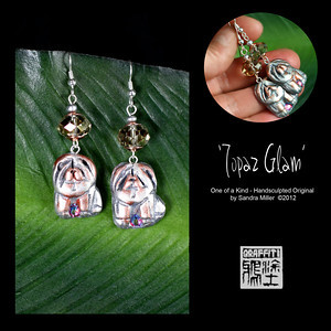 "TOPAZ GLAM EARRINGS  Faux silver and bronze shaded chows are hand sculpted from polymer clay to create a light as air pair of earrings!  The Topaz glass crystal the chows dangle from is a light catching magnet and the dogs feature a rose Swarovski crystal between their paws!!!!  Neutral in color and extremely versatile, these little chowlings can be dressed up or down according to your mood.    EARRINGS MEASURE 1 1/2"" long x 3/4"" wide without wire"