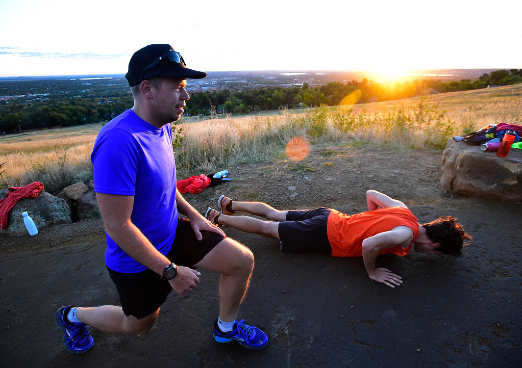 . Brad Dober does lunges as Andrew Alder does pushups as the sun comes up at the Ascenders Project workout at Chautauqua in Boulder on Wednesday September 12, 2018.  For more photos go to dailycamera.com (Photo by Paul Aiken/Staff Photographer)