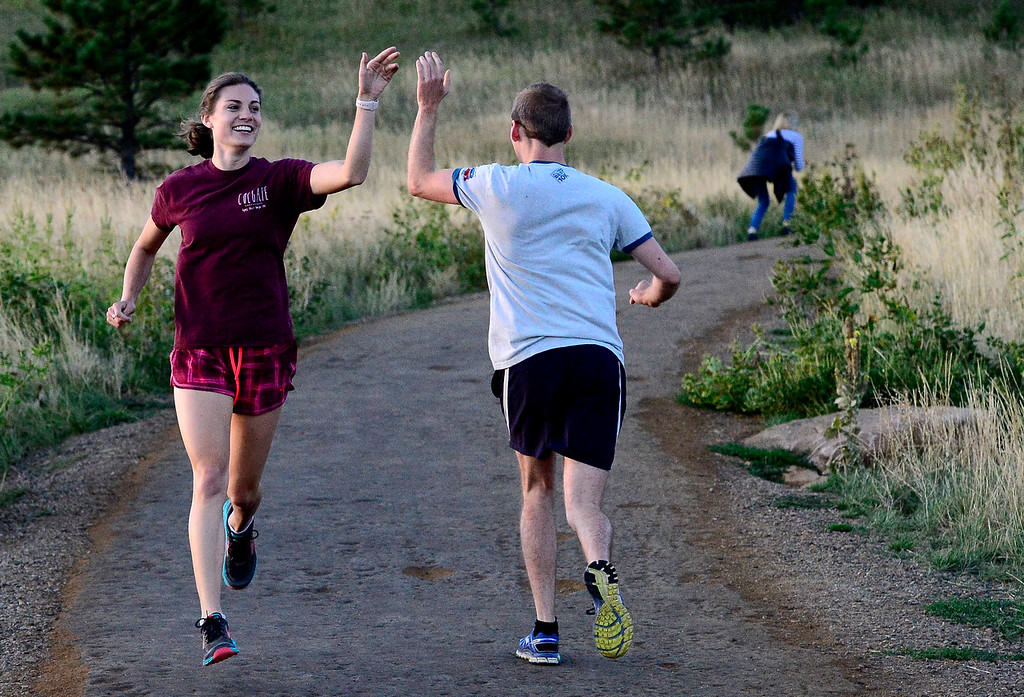 . Mikhaila Redovian high fives TJ Kirk as they work the running portion of the the Ascenders Project workout at Chautauqua in Boulder on Wednesday September 12, 2018.  For more photos go to dailycamera.com (Photo by Paul Aiken/Staff Photographer)