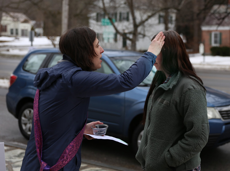 HOLLY PELCZYNSKI - BENNINGTON BANNER St. James Episcopal Church reverend Kathleen Moore blesses Larisa Dodge of Bennington with ashes on her forehead during her lunch break on Wednesday afternoon during the Ashes To Go service