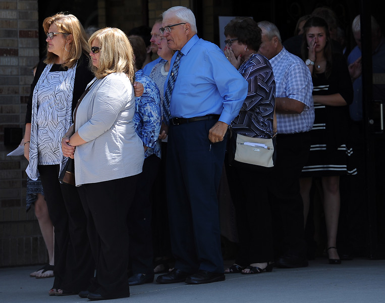 Ashley Doolittle's mother, Ann Marie Doolittle, center left, is surrounded by friends and family as she watches pallbearers load Ashley's casket into the hearse after her funeral mass Friday, June 17, 2016, at Saint John the Evangelist Catholic Parish in Loveland. (Photo by Jenny Sparks/Loveland Reporter-Herald)
