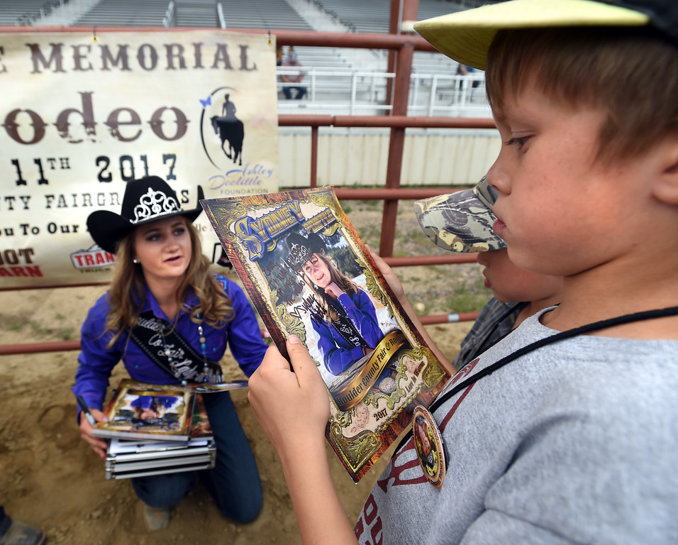 . Sydney Postale signs her photos for Seth Anderson during the Ashley Doolittle Memorial Rodeo on June 10, 2017. For more photos, go to www.dailycamera.com. Cliff Grassmick / Staff Photographer/ June 10, 2017