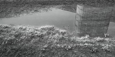 Farmstead - building - silo - reflection in field-road pool of water