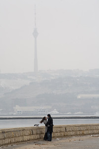 Baku, Azerbaijan - February 2008: Young couple in Baku, Azerbaijan along the shore of the Caspian embrace with the TV tower in the background. (Photo by Christopher Herwig)