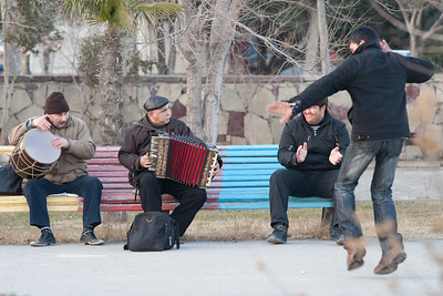 Baku, Azerbaijan - February 2008: A passerby dances to tradinal Azeri music played by three men on a bench along the shores of the Caspian Sea in Baku, Azerbaijan. (Photo by Christopher Herwig)