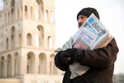 Baku, Azerbaijan - February 2008:  Man selling newspapers in front of Dom Soviet on Azadliq Square on the shore of the Caspian Sea in the capital city of Baku, Azerbaijan.  The massive building is a blend of Soviet and Islamic architectural influences and served as the government headquarters during the USSR.  (Photo by Christopher Herwig)