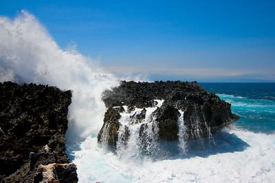 Ocean waves crushing against cliff