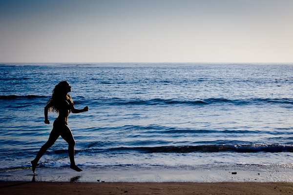 Healthy life concept - sporty woman running along beach
