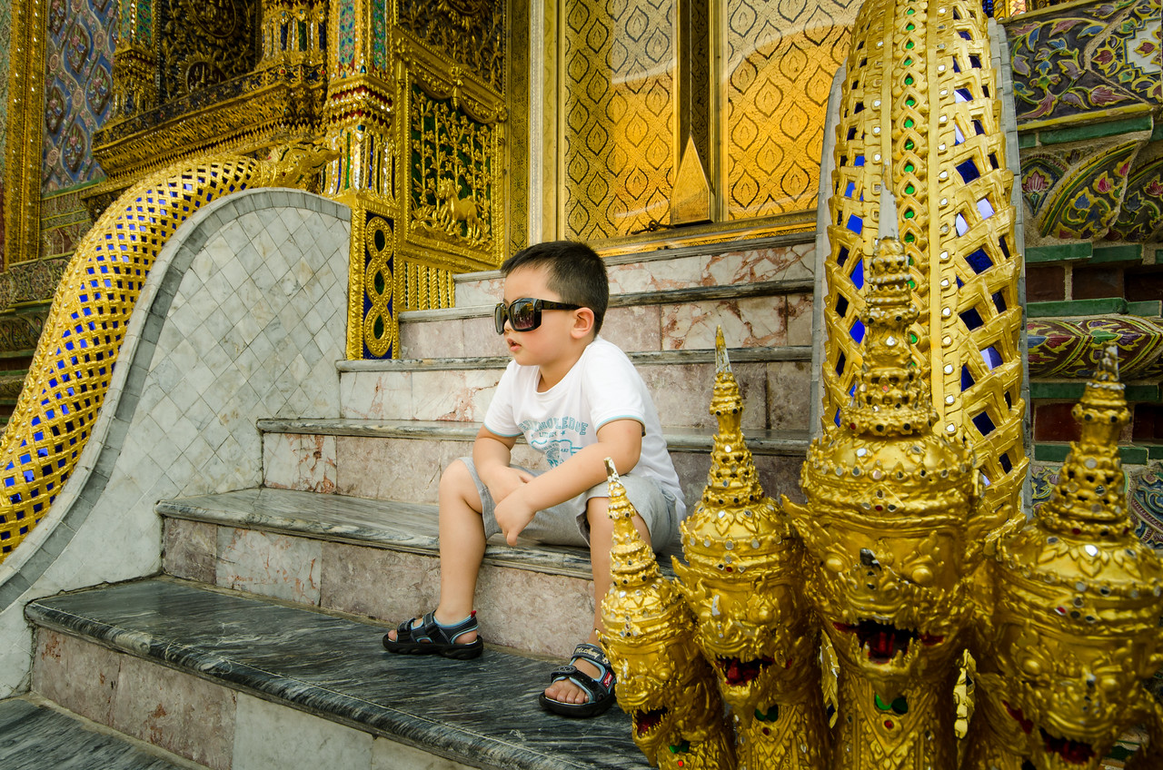 A young tourist takes a break outside the Temple of the Emerald Buddha.