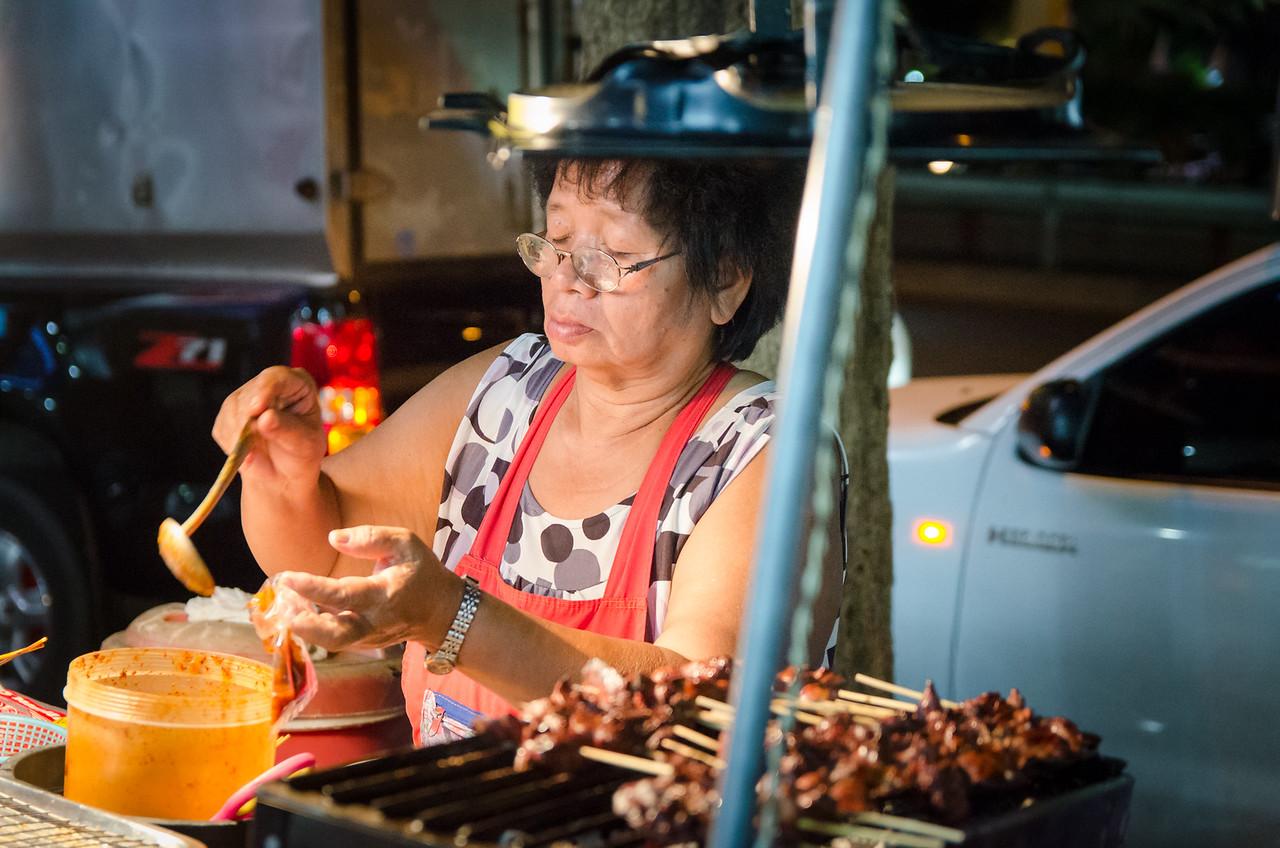 Lady making street food.