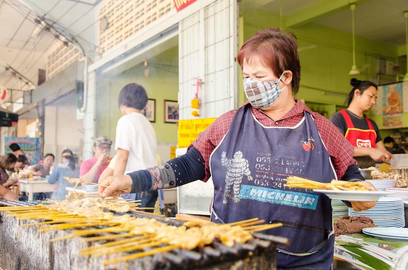 Woman making chicken satay in Chiang Mai.