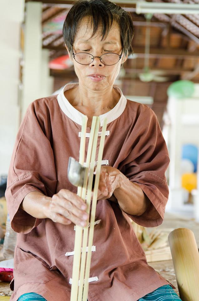 Woman splitting bamboo to make umbrella ribs.