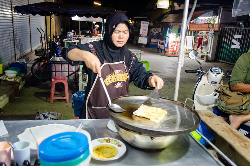 Muslim woman makes roti on the street.
