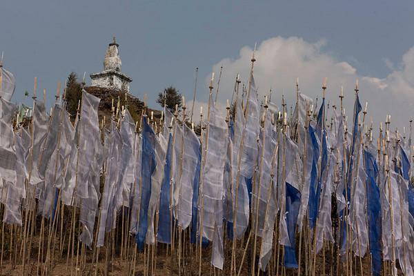 Prayer flags line the hillside below the chorten
