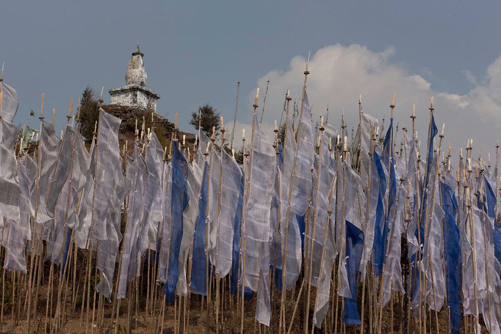 Prayer flags line the hillside below the chorten