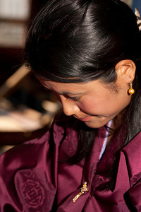 A young girl concentrating on her weaving