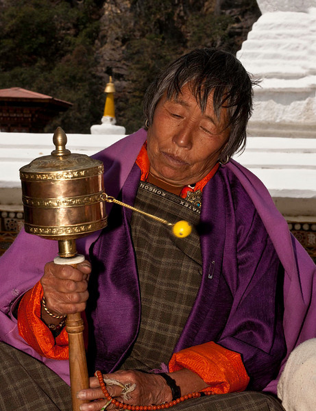 Contemplating her prayers and the prayer wheel